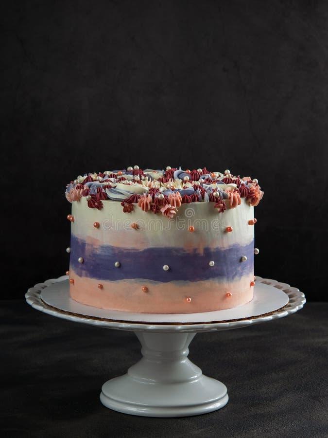 Moderiktig festlig färgrik kaka på kakaställning över mörk bakgrund med fritt utrymme för text som är vertikalt royaltyfria foton