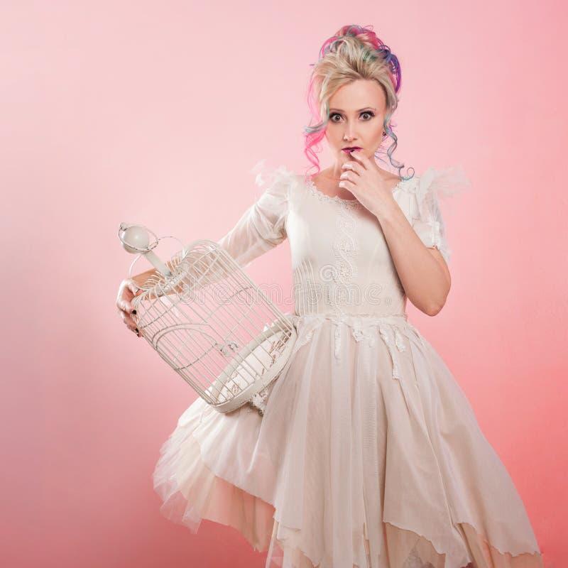 Moderiktig flicka i den vita klänningen Idérik hårfärgläggning Mång--färgad frisyr Begrepp med en tom fågelbur arkivbilder