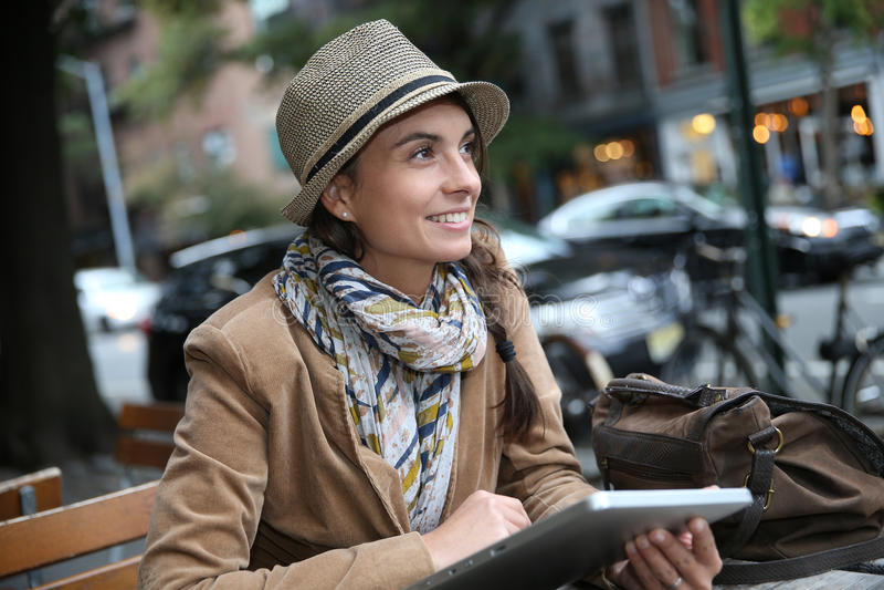 Moderiktig flicka med minnestavlan i kafé royaltyfri fotografi