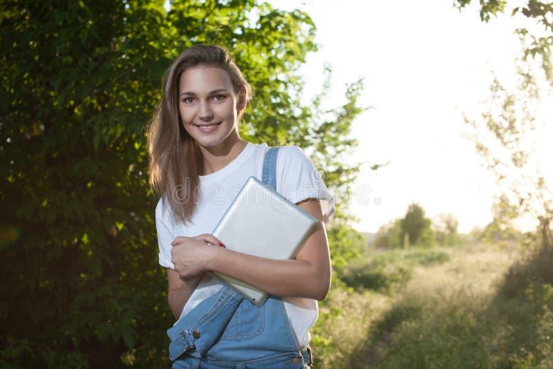 Moderiktig flicka som använder en minnestavlaPC arkivfoto