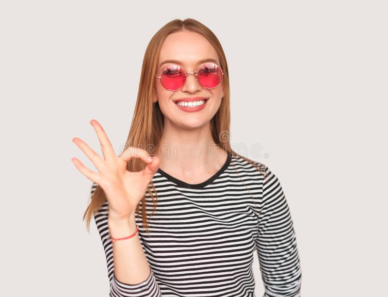 Moderiktig flicka som visar reko gest på vit royaltyfri fotografi