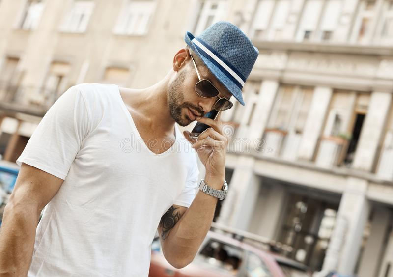 Moderiktig grabb på telefonen på gatan i stad royaltyfria bilder