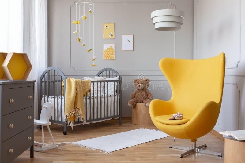 Moderiktig gul äggstol i elegant grå barnkammare arkivfoto