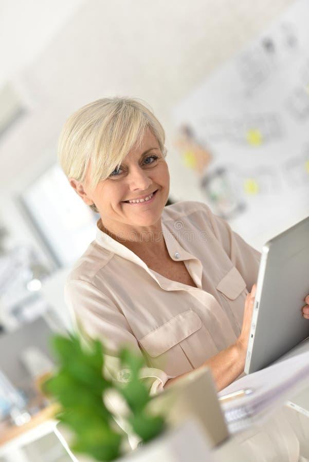 Moderiktig hög affärskvinna på kontoret som arbetar på minnestavlan arkivbild