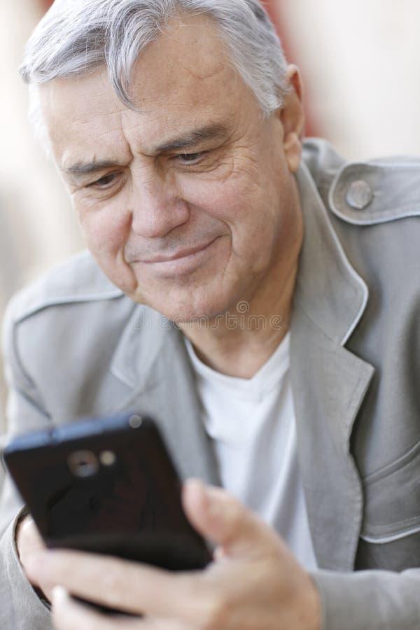 Moderiktig hög man som använder smarthone arkivfoto