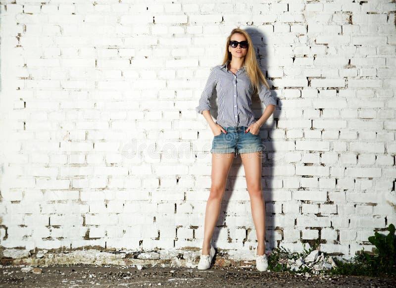 Moderiktig Hipsterflicka på tegelstenväggen arkivfoton