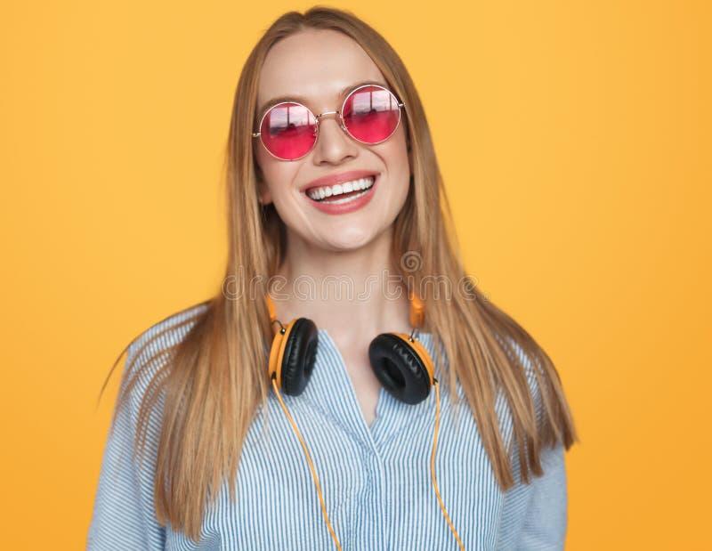 Moderiktig hipsterkvinna i hörlurar och solglasögon arkivfoton