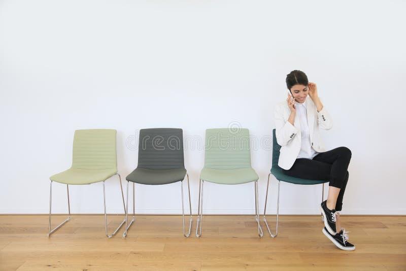 Moderiktig kvinna i väntande rum på telefonen fotografering för bildbyråer