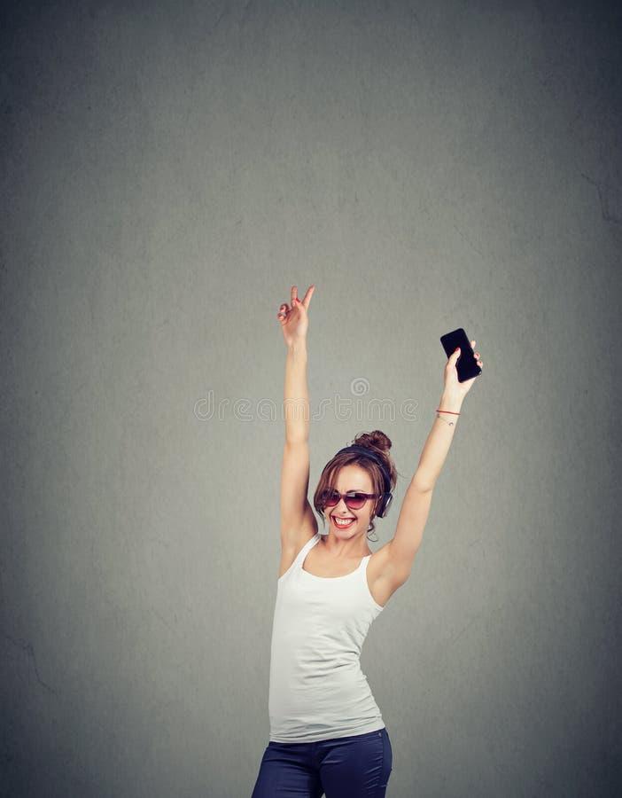 Moderiktig kvinna med telefonen och hörlurar arkivfoto