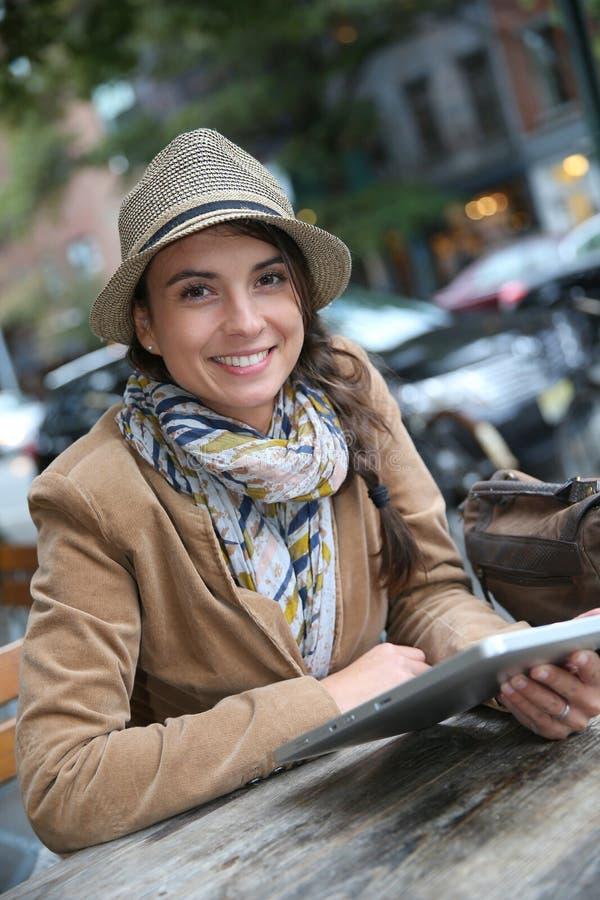 Moderiktig kvinna som använder minnestavlan i coffee shop royaltyfri fotografi