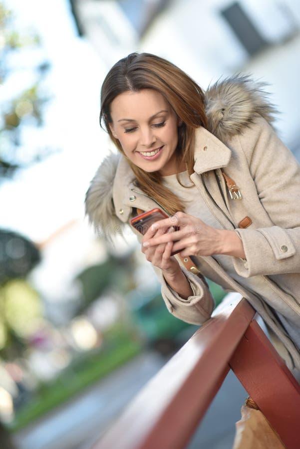 Moderiktig kvinna som använder utomhus smartphonen royaltyfri fotografi