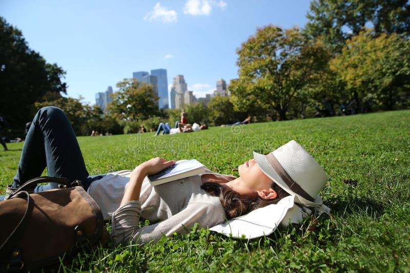 Moderiktig kvinna som kopplar av i gräs i staden arkivbild