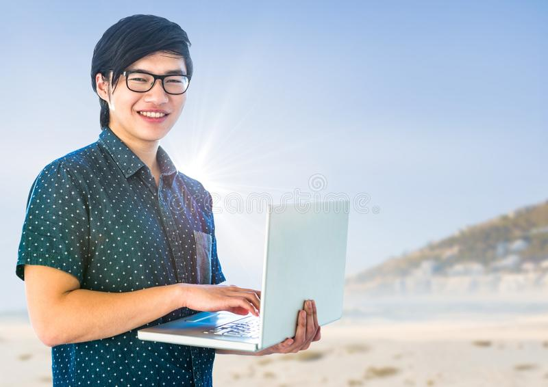 Moderiktig man med bärbara datorn mot den oskarpa stranden royaltyfri foto