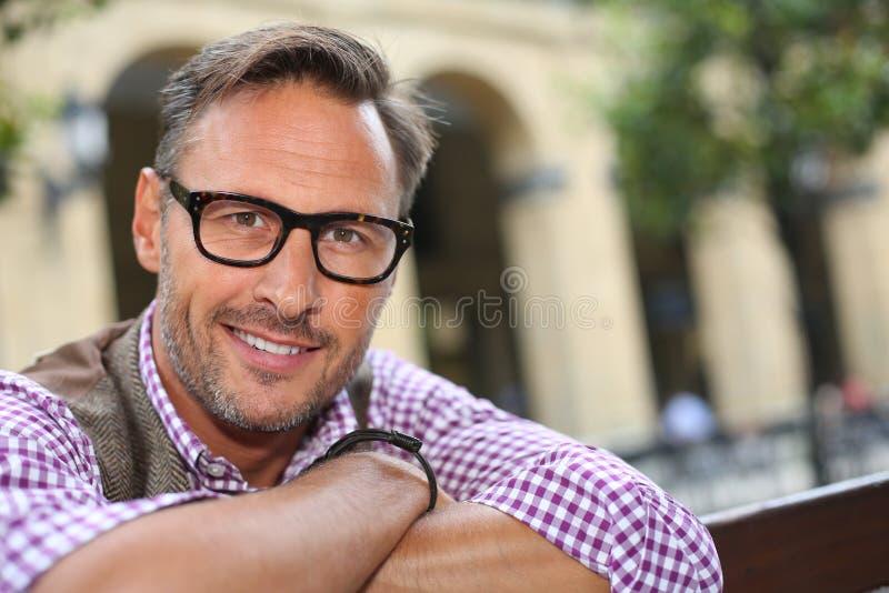 Moderiktig man med glasögon som ser kameran royaltyfri bild