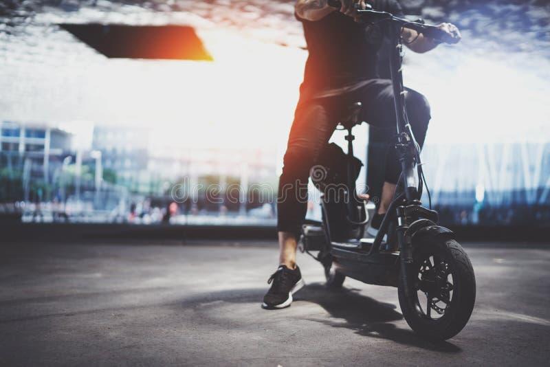 Moderiktig manhipster som förbereder sig för ritt med den elektriska sparkcykeln i staden Innovativ transport arkivfoto