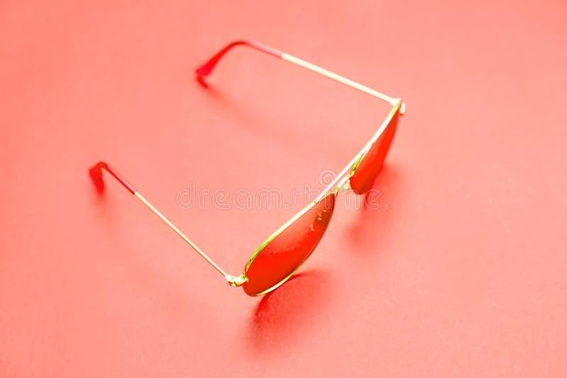 Moderiktig orange solglasögon på en orange bakgrund semester f?r sommar f?r strandbegreppssn?ckskal fotografering för bildbyråer