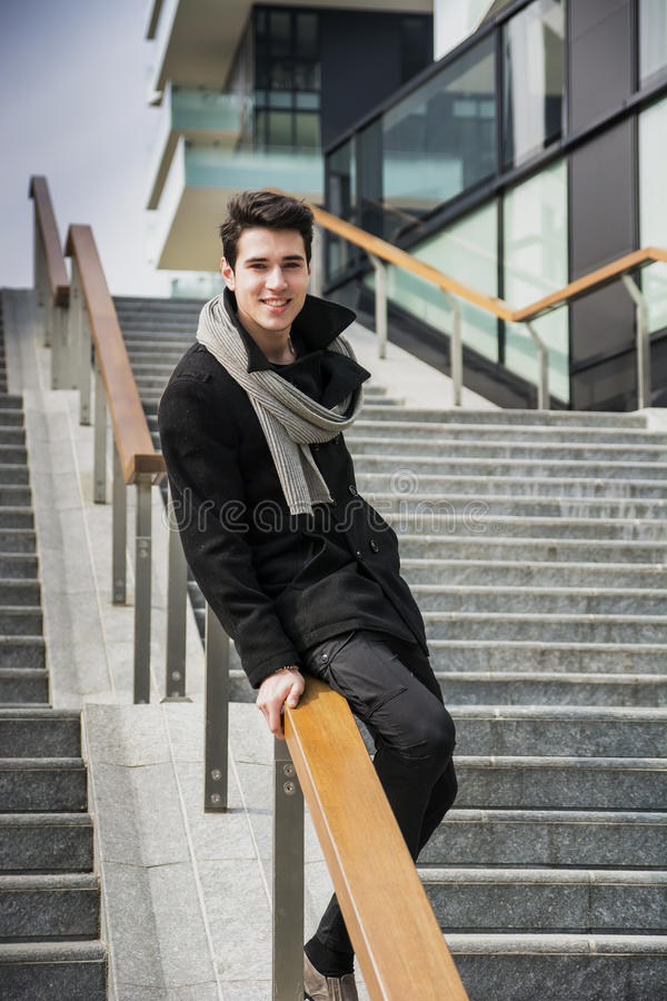 Moderiktig stilig ung man i vintermodeanseende på en lång trappuppgång arkivfoto