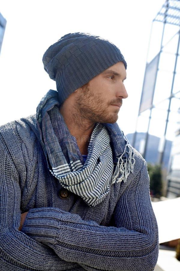 Moderiktig ung man i hatt och scarf arkivfoton