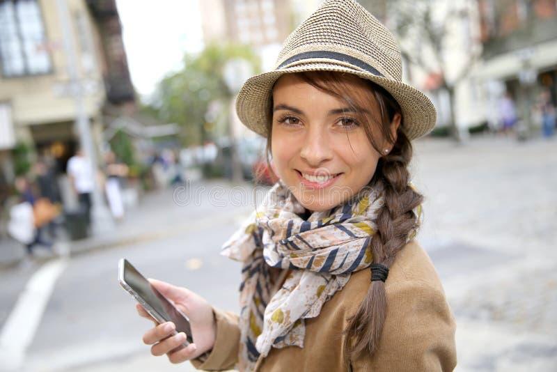 Moderiktig ung stilfull kvinna med smartphonen royaltyfri foto