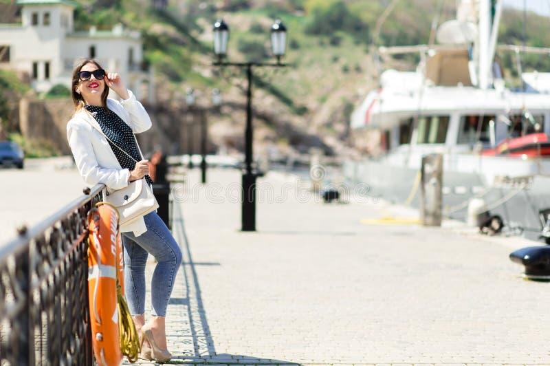 Moderiktig vit dräkt av den härliga skratta kvinnan i solglasögon som poserar på den vita yachtbakgrunden royaltyfri bild