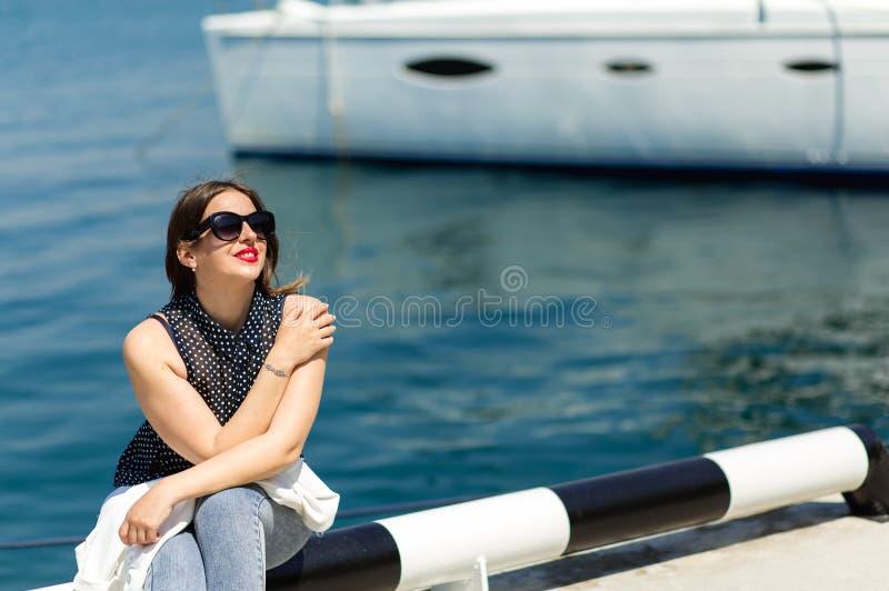 Moderiktig vit dr?kt av den h?rliga skratta kvinnan i solglas?gon som poserar p? den vita yachtbakgrunden royaltyfri bild