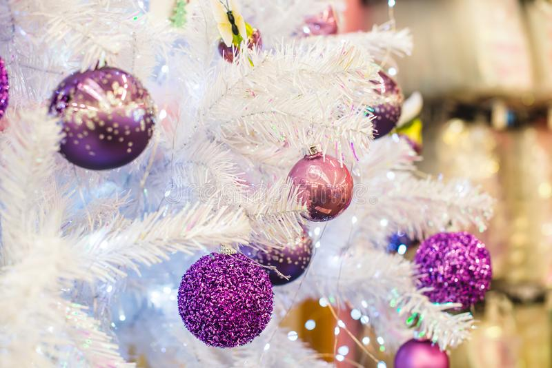 Moderiktiga purpurfärgade ultravioletta kulöra struntsaker försilvrar på den vita konstgjorda julgranen close upp Selektiv fokus, royaltyfri fotografi