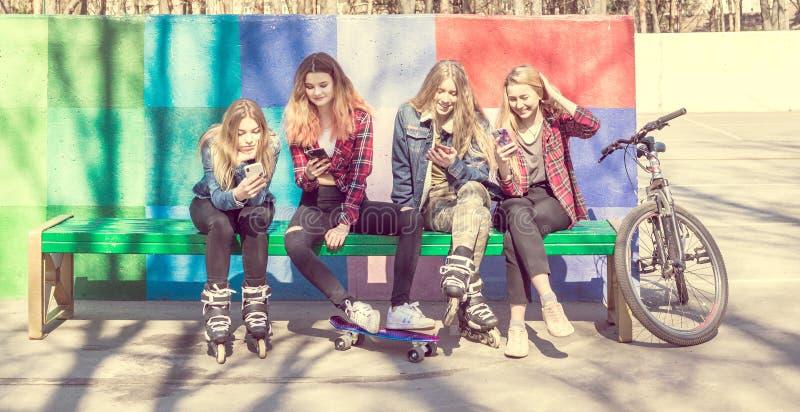 Moderiktiga unga flickor i en skateboard parkerar royaltyfria bilder