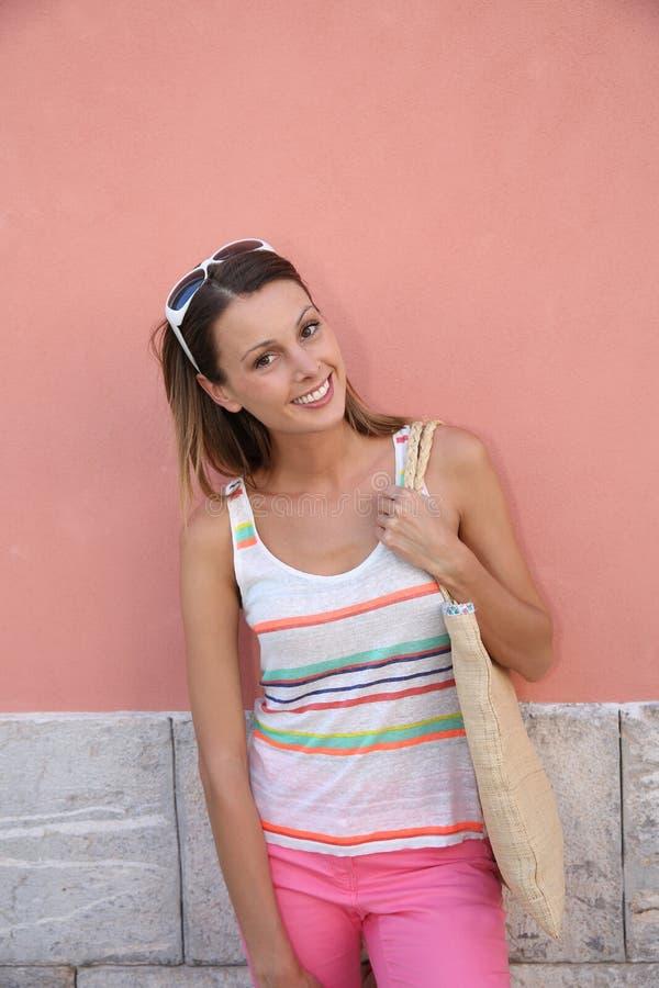 Moderiktigt flickaanseende vid den rosa väggen utomhus royaltyfri foto