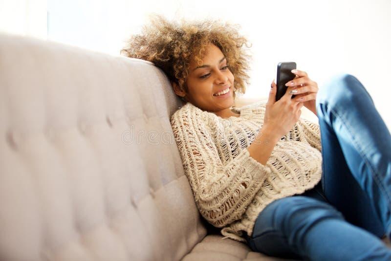 Moderiktigt sammanträde för ung kvinna som är hemmastatt och ser mobiltelefonen royaltyfria foton