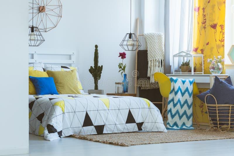 Moderiktigt sovrum med gul tillbehör arkivfoton