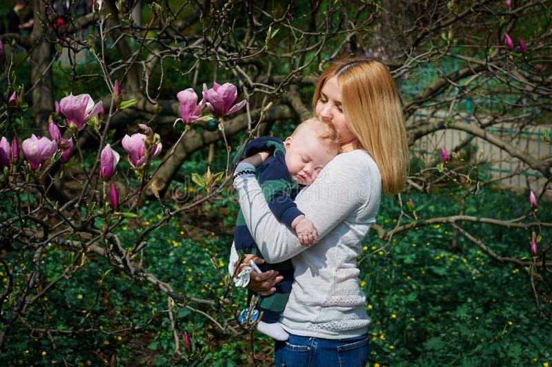 Moderinnehavet behandla som ett barn i den blommande magnoliaträdgården royaltyfria foton