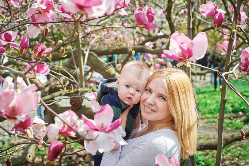 Moderinnehavet behandla som ett barn i den blommande magnoliaträdgården arkivfoto