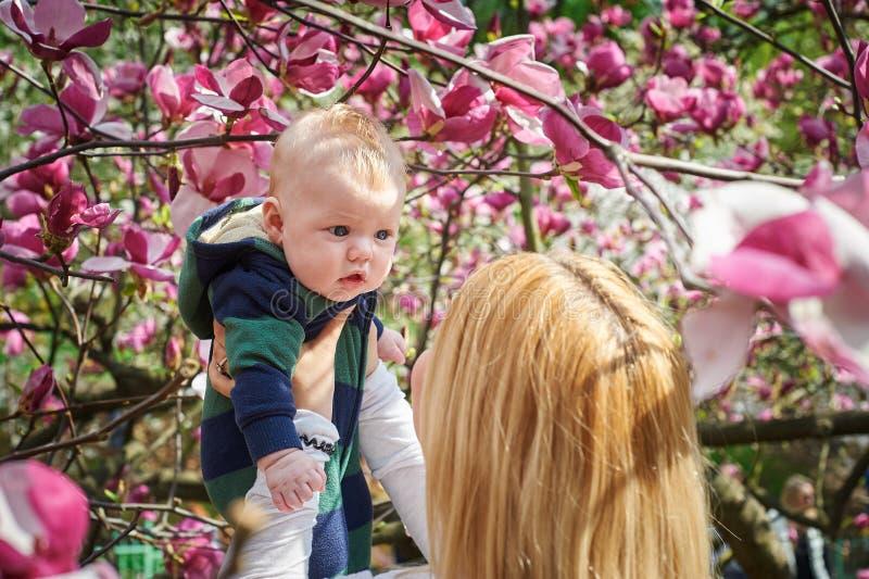 Moderinnehavet behandla som ett barn i den blommande magnoliaträdgården royaltyfri bild