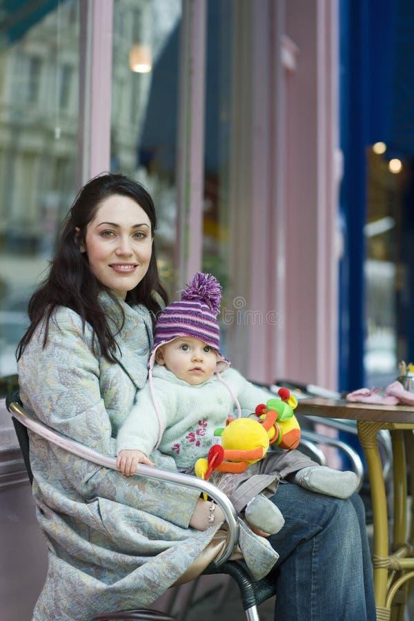 Moderinnehavet behandla som ett barn på Lap Sitting In Outdoor Cafe arkivbilder