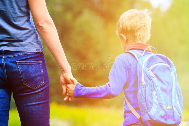 Moderinnehavhand av den lilla sonen med ryggsäcken royaltyfria foton