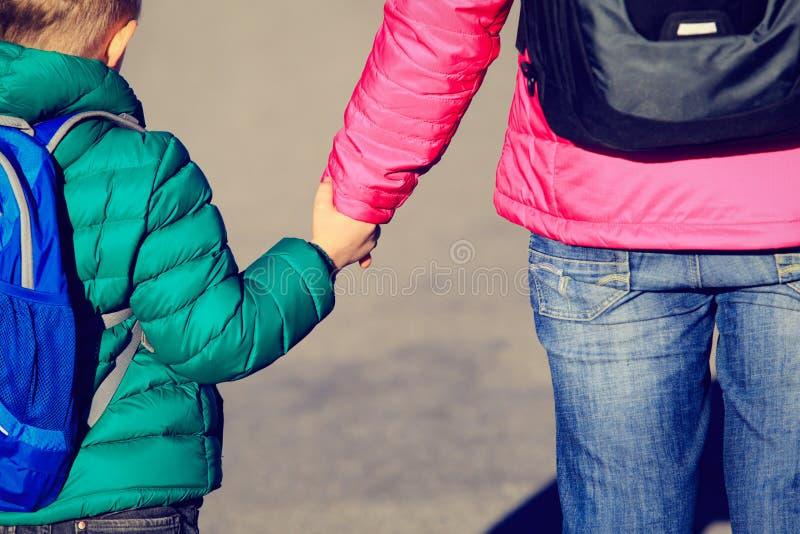 Moderinnehavhand av den lilla sonen med ryggsäcken på vägen royaltyfri bild