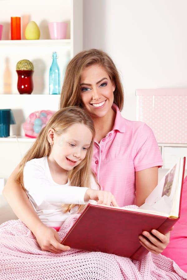 Moderläsebok med barnet arkivbild