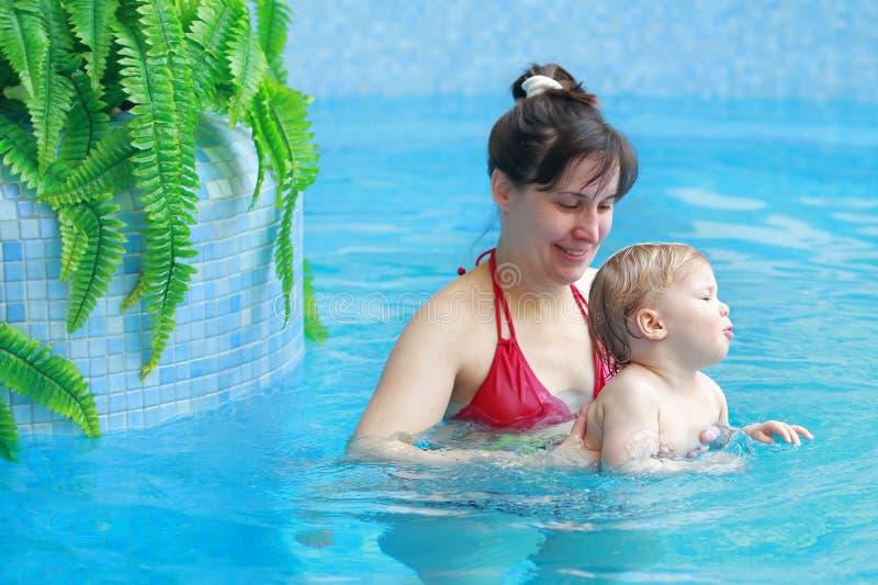 Moderlek med hennes barn i simbassäng royaltyfri bild