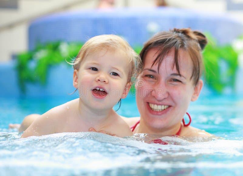 Moderlek med hennes barn i simbassäng fotografering för bildbyråer