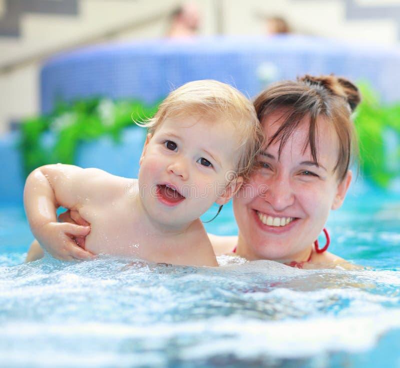 Moderlek med hennes barn i simbassäng royaltyfri foto