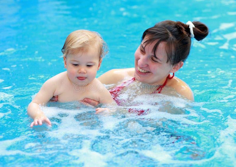 Moderlek med hennes barn i simbassäng arkivbild