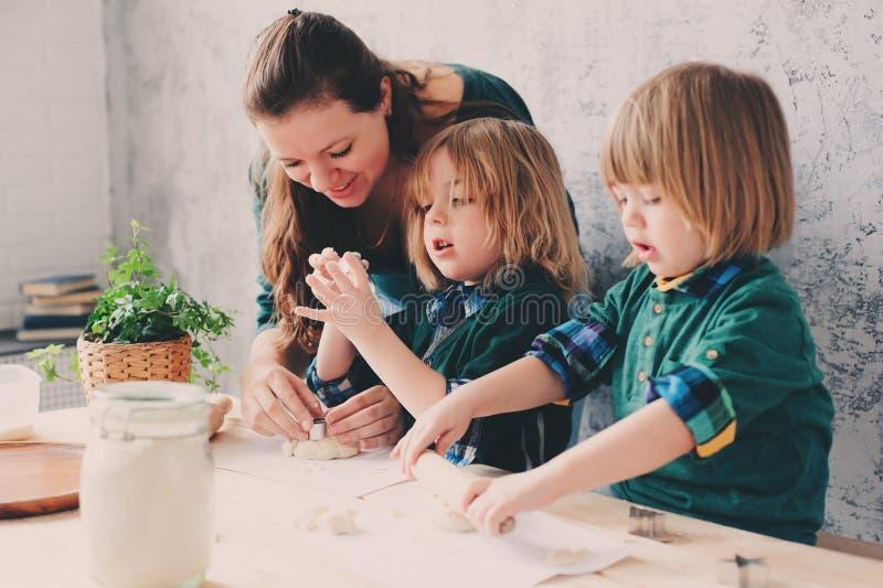 Modermatlagning med ungar i kök Litet barnsyskon som tillsammans bakar och spelar med hemmastadd bakelse arkivbilder
