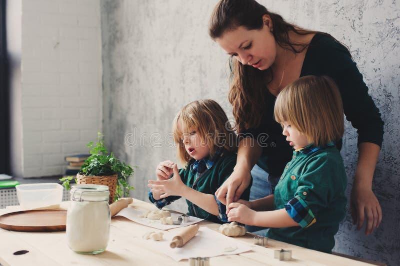 Modermatlagning med ungar i kök Litet barnsyskon som tillsammans bakar och spelar med hemmastadd bakelse arkivfoton
