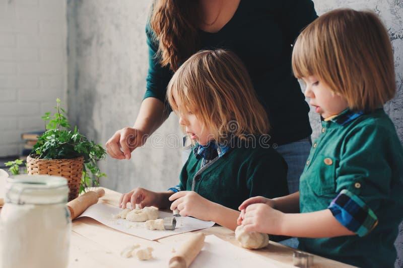 Modermatlagning med ungar i kök Litet barnsyskon som tillsammans bakar och spelar med hemmastadd bakelse fotografering för bildbyråer
