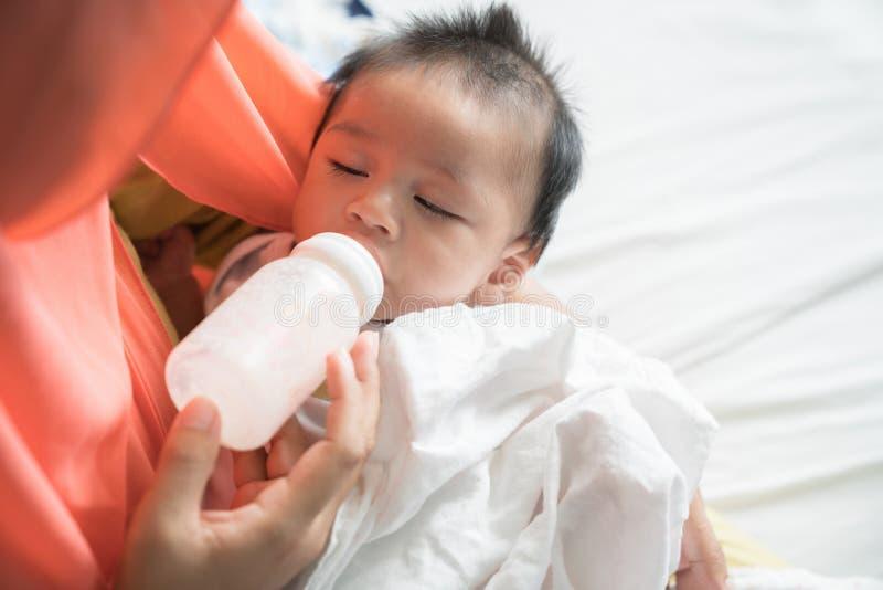 Modermatning behandla som ett barn med mjölkar flaskan royaltyfria bilder