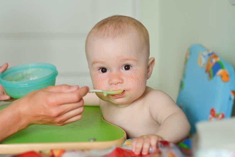 Modermatning behandla som ett barn pojken hemmastatt kök arkivbild