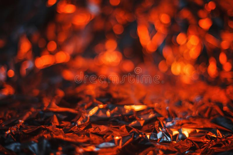 Modern abstract foil background lit by colorful red and orange l royalty free stock image