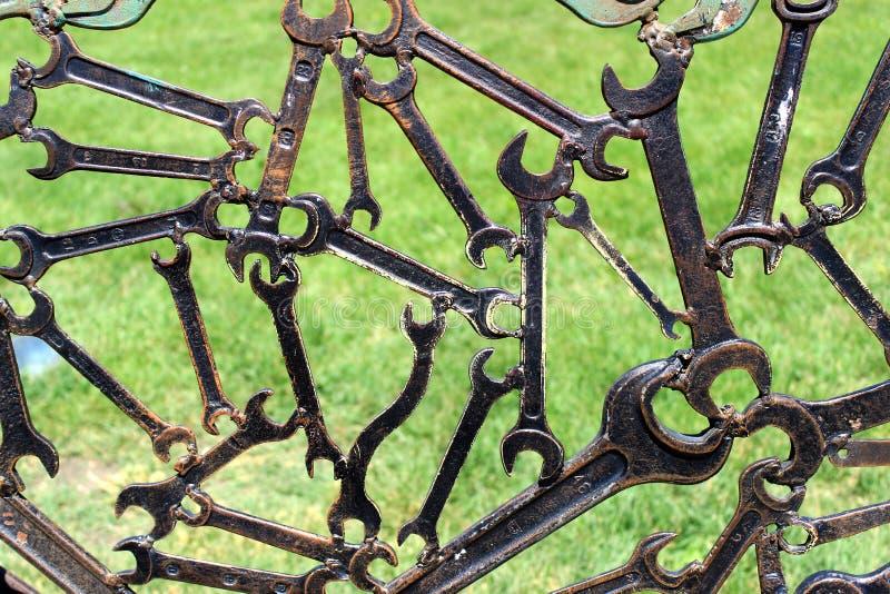Modern abstrakt industriell bakgrund från skruvnycklar för svetsad metall med gräs bakom arkivbild