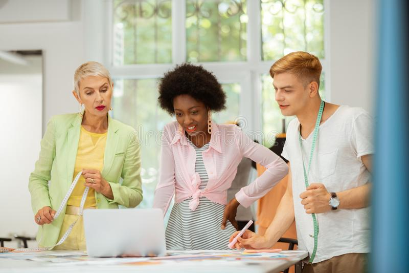Modern active fashion designers looking at fabric samples stock photography