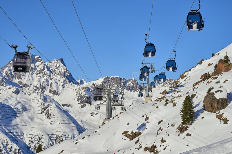 Modern aerial tramway in Austrian Alps ski resort. Highland cable car leads between hills from village to ski slope. Ischgl, Austria - December 25, 2017: Modern royalty free stock images